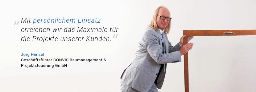 """CONVIS-Geschäftsführer Jörg Hensel schiebt einen Fensterrahmen vor sich her und sagt: """"Mit persönlichem Einsatz erreichen wir das Maximale für die Projekte unserer Kunden."""""""