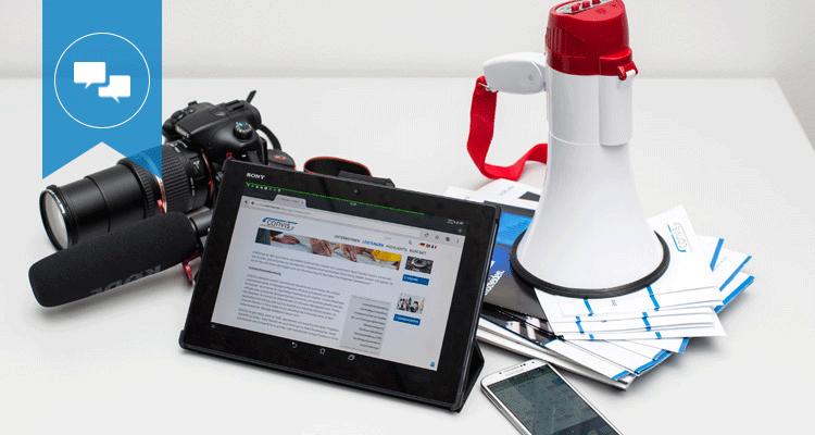 Verschiedene Broschüren, iPad, Smartphone, Fotoapparat und Aufnahmegerät liegen auf dem Tisch, um Kommunikation und Marketing von Großprojekten zu repräsentieren.
