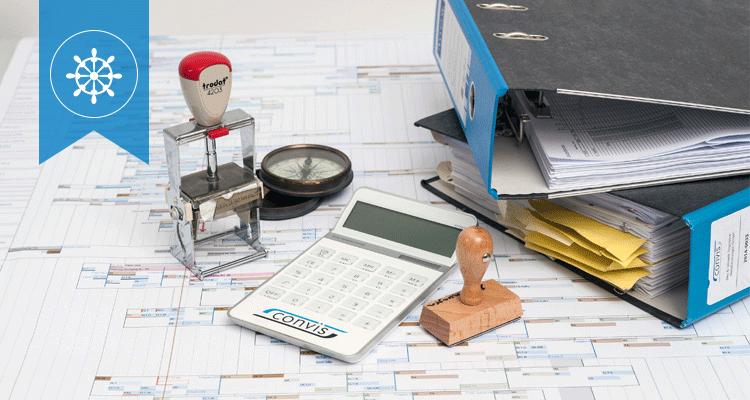 Verschiedene Elemente auf einem Tisch zur Symbolisierung der Projektsteuerung: u.a. Baupläne, Ordner, Stempel, Kompass.